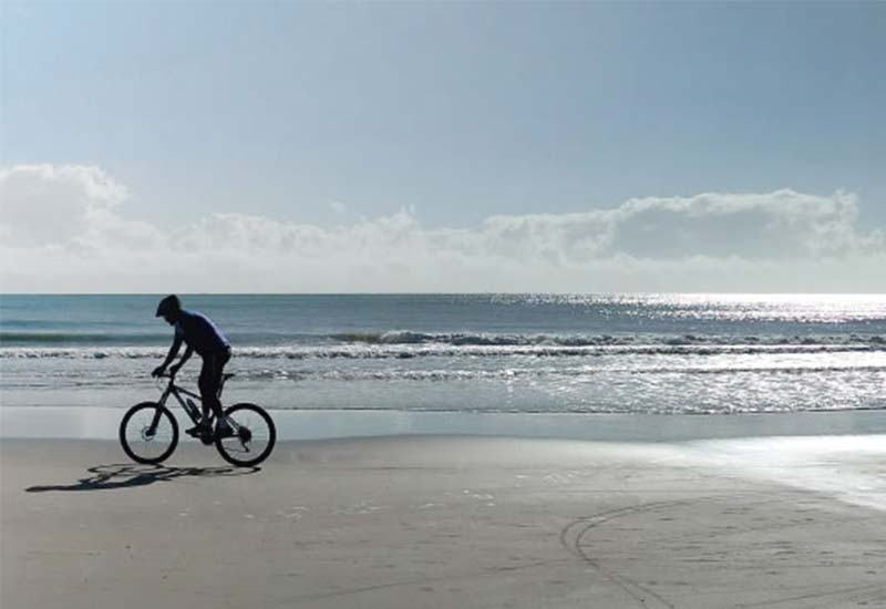 Person on a bike rented from Bike and go on the beaches of Bibione