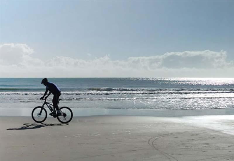 Persona su bicicletta noleggiata da Bike and go sulle spiaggie di Bibbione